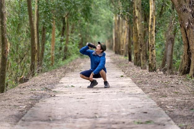 Asiatischer läufer in der sportklage laufen mit der glückaktion, die das wasser vom sport trinkt
