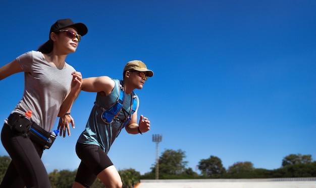 Asiatischer läufer probt das joggen und läuft auf dem spielfeld