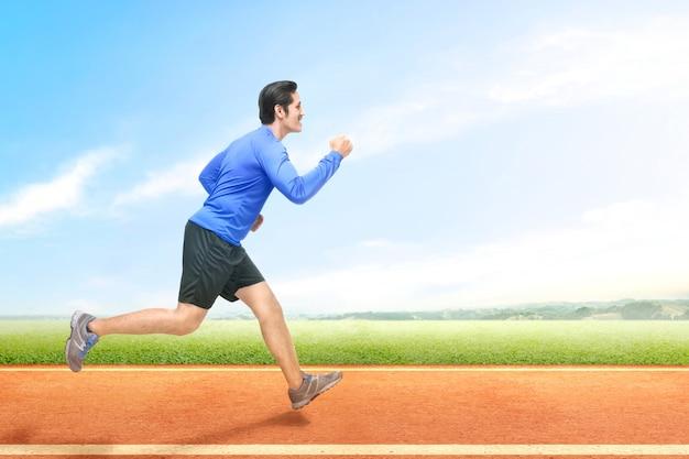 Asiatischer läufermann, der auf der laufbahn läuft