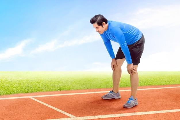 Asiatischer läufermann machen eine pause, nachdem er auf der laufbahn gelaufen ist