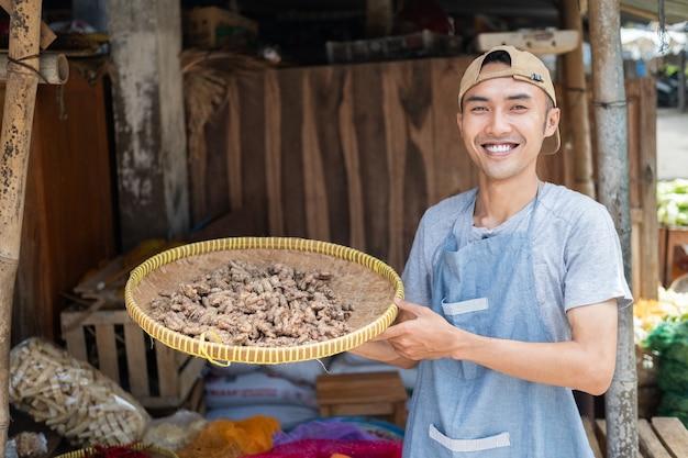 Asiatischer lebensmittelhändler, der ein gewebtes bambustablett mit kräutern an einem gemüsestand hält