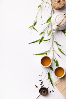 Asiatischer lebensmittelhintergrund stellte mit grünem tee, schalen und teekanne mit bambusniederlassungen ein