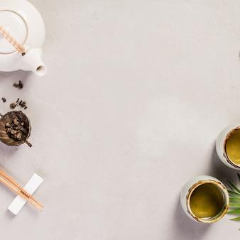 Asiatischer lebensmittelhintergrund - tee und stäbchen, platz für text