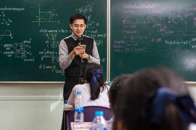 Asiatischer lehrer, der das intelligente mobiltelefon verwendet, um lektion über die physikformel zu geben