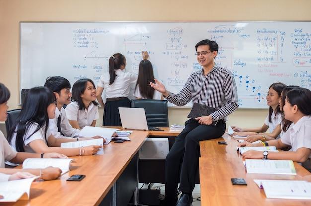 Asiatischer lehrer, der der gruppe studenten im klassenzimmer lektion gibt