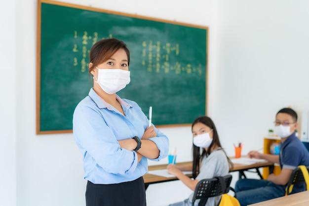 Asiatischer lehrer, der eine gesichtsmaske im klassenzimmer trägt
