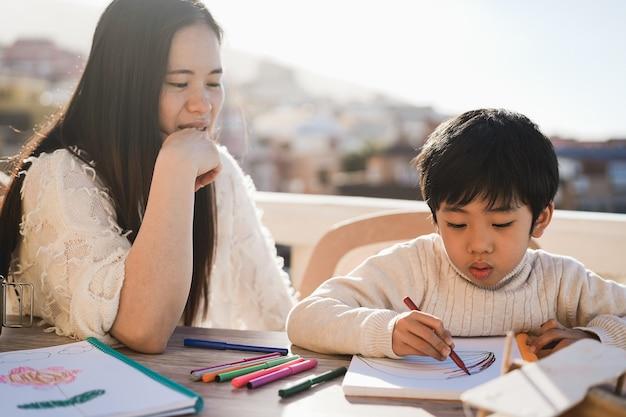 Asiatischer lehrer, der mit kinderjunge an der vorschule im freien im sonnigen sommertag arbeitet