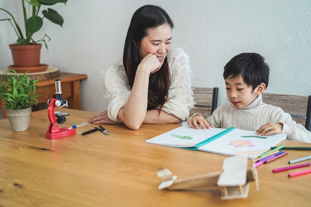 Asiatischer lehrer, der mit kindjunge an der vorschule arbeitet - fokus auf frauengesicht