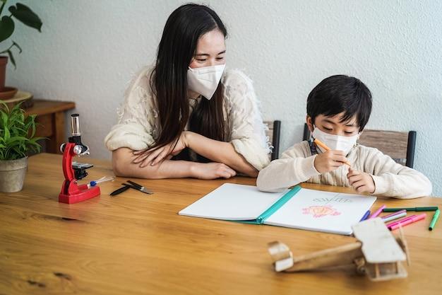 Asiatischer lehrer und kind tragen schützende gesichtsmasken im klassenzimmer während des ausbruchs des coronavirus - fokus auf jungengesicht