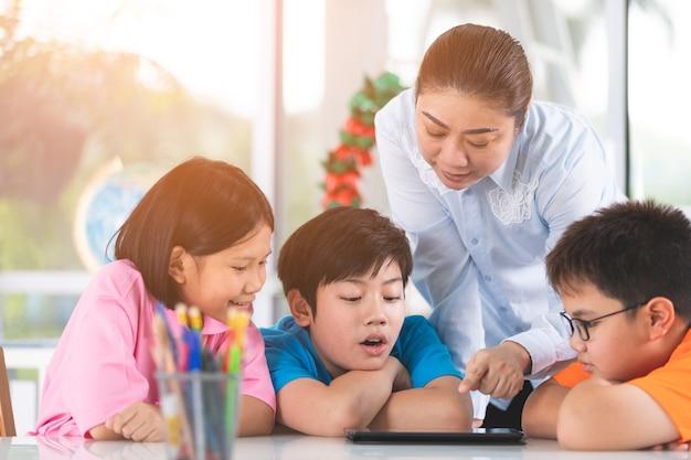 Asiatischer lehrer und kinder, die unter verwendung der digitalen tablette sich unterhalten