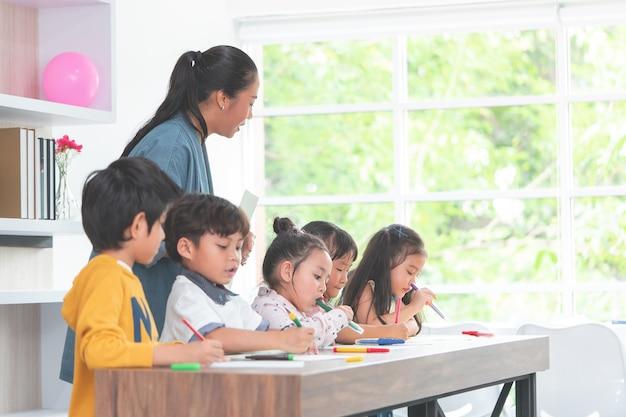 Asiatischer lehrer unterrichtet kinder im kindergartenklassenzimmer