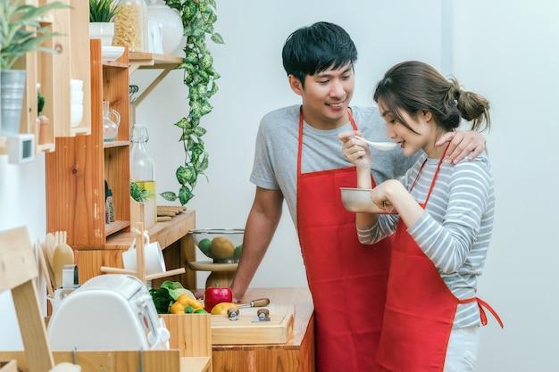 Asiatischer liebhaber oder paare, die lebensmittel im küchenraum am modernen haus, an den paaren und an l kochen und schmecken