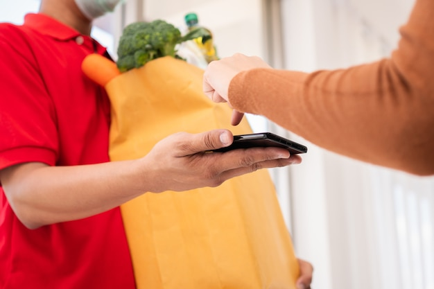 Asiatischer lieferbote, der eine tüte frisches essen für das geben an kunden und das halten des smartphones für das empfangen von zahlungen zu hause hält