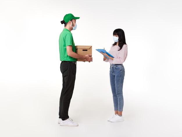 Asiatischer lieferbote, der gesichtsmaske in grüner uniform mit paketbox trägt, geben frau kostüm über weiß.