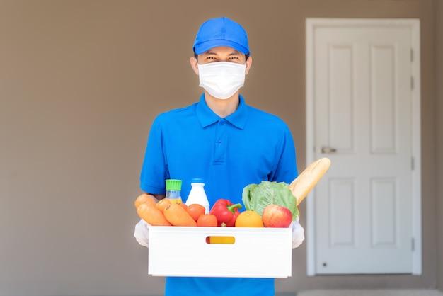 Asiatischer lieferbote, der gesichtsmaske und handschuh mit lebensmittelbox von lebensmitteln, obst, gemüse und getränken trägt, die vor dem kundenhaus während der zeit der hausisolation stehen.