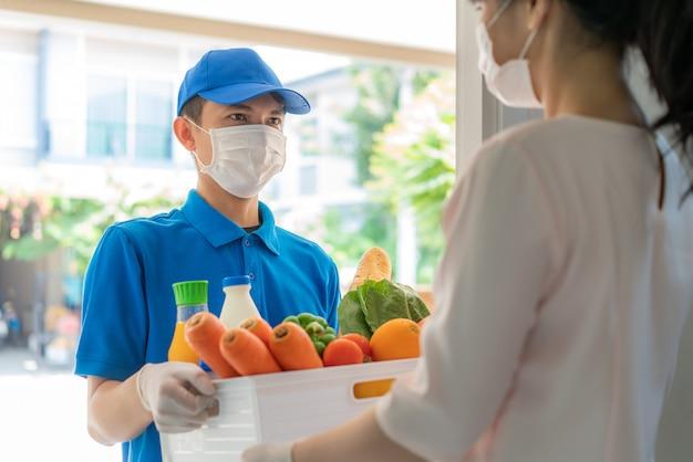 Asiatischer lieferbote, der gesichtsmaske und handschuh mit lebensmittelschachtel von lebensmitteln, obst, gemüse und getränk trägt, geben frau kostümier vor dem haus während der zeit der hausisolation.