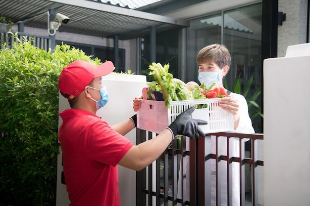 Asiatischer lieferbote, der gesichtsmaske und handschuhe in der roten uniform trägt, die lebensmittelbox liefert