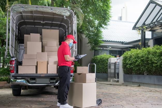 Asiatischer lieferbote, der gesichtsmaske und handschuhe in der roten uniform trägt, die paketverpackung zum empfänger während des covid-19-ausbruchs liefert