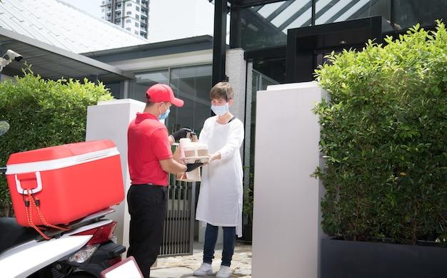 Asiatischer lieferbote, der gesichtsmaske und handschuhe in der roten uniform trägt, die tasche von essen und trinken liefert