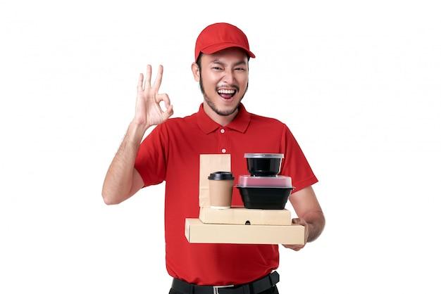 Asiatischer lieferbote, der in der roten uniform hält, die brotdose und kaffee zum mitnehmen über weißem hintergrund hält. express-lieferservice während covid19.