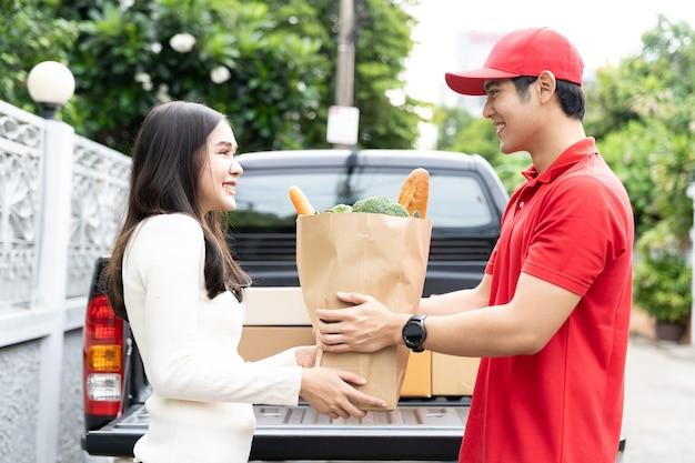 Asiatischer lieferbote, der rote uniform, roten hut hält papiertüte trägt