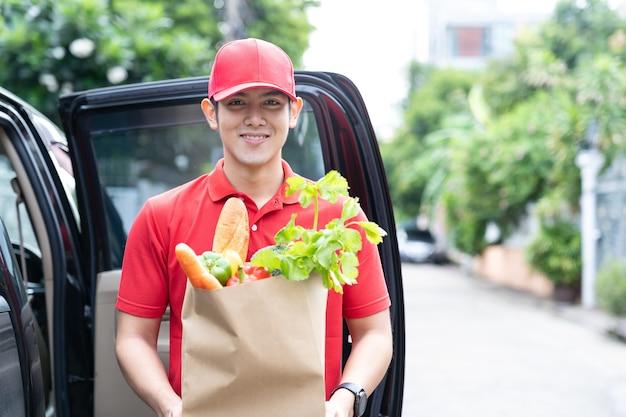 Asiatischer lieferbote, der rote uniform und roten hut trägt, der papiertüte des essens, des obstes, des gemüses lächelnd hält und nahe der autotür vor dem haus steht.