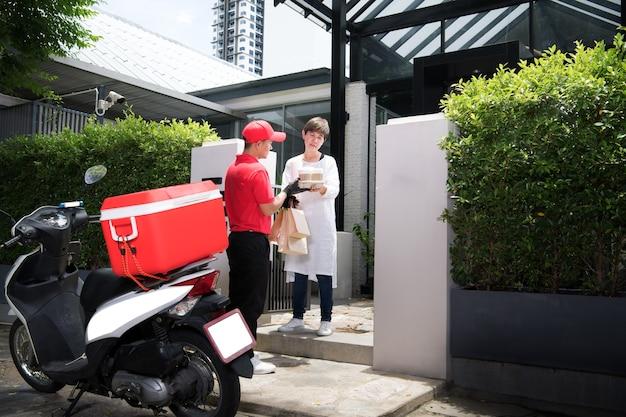 Asiatischer lieferbote in der roten uniform, die lebensmittelbeutel der nahrung, des obstes, des gemüses und des getränks zum empfänger der frau zu hause liefert