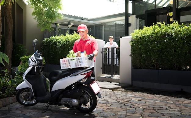 Asiatischer lieferbote in der roten uniform, die lebensmittelschachtel des lebensmittels, des obstes, des gemüses und des getränks zum empfänger der frau zu hause liefert