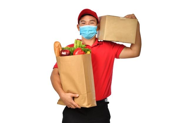 Asiatischer lieferbote in roter uniform, medizinische gesichtsmaske, schutzhandschuhe tragen paket