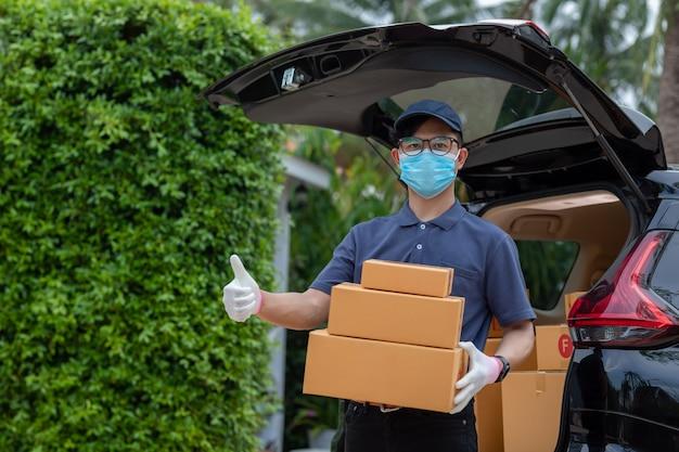 Asiatischer lieferbote mitarbeiter in blauer kappe t-shirt uniform maske handschuh halten paketbox. concept service quarantäne-pandemie-coronavirus-virus [covid-19]