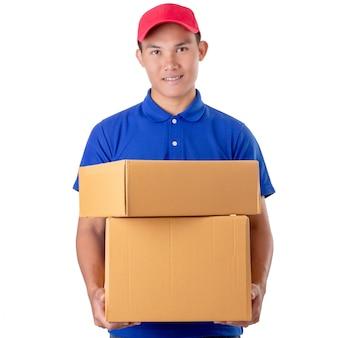Asiatischer lieferbote tragen die braunen paket- oder pappschachteln, die auf weiß lokalisiert werden