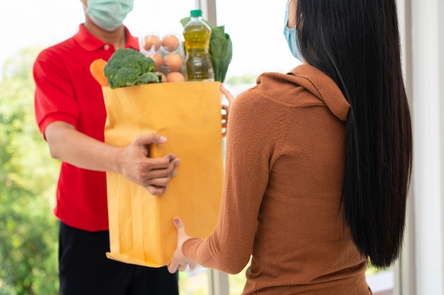 Asiatischer lieferbote vom supermarkt, der eine gesichtsmaske trägt und eine tüte frisches essen hält