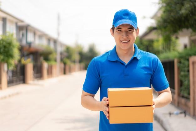 Asiatischer lieferjunge im blauen einheitlichen lächeln und im halten des stapels von pappkartons im vorderhausdorf mit kopienraum.