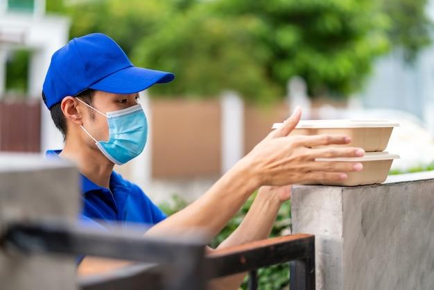 Asiatischer liefern mann mit gesichtsmaske im blauen hemd, das lebensmittelboxen kontaktlos behandelt