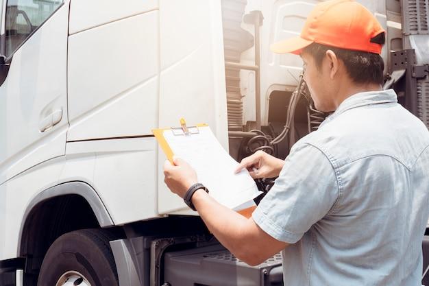 Asiatischer lkw-fahrer, der zwischenablage hält, die checkliste der sicherheitsfahrzeugwartung des sattelschleppers prüft