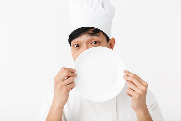 Asiatischer lustiger hauptmann in der weißen kochuniform, die an der kamera lächelt, während eine platte lokalisiert über weißer wand hält