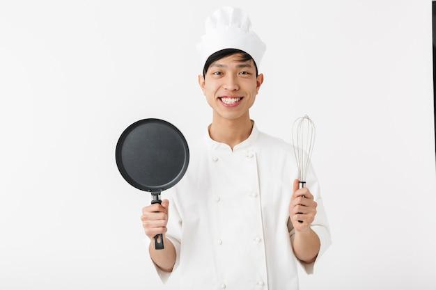Asiatischer lustiger hauptmann in der weißen kochuniform, die an der kamera lächelt, während kochwerkzeuge lokalisiert über weißer wand halten