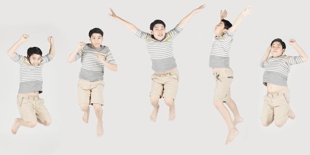 Asiatischer lustiger kinderjunge, der auf grauen hintergrund springt.
