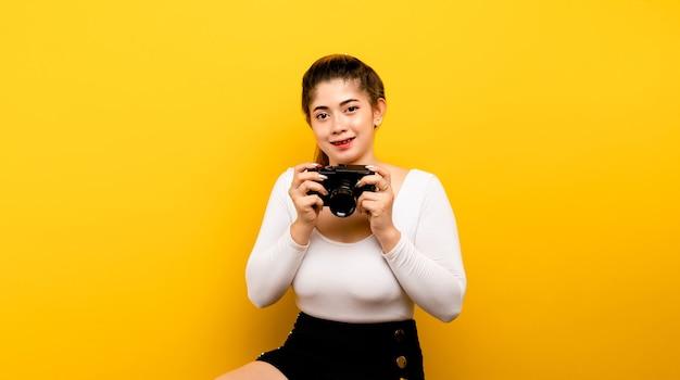 Asiatischer mädchenfotograf mit seiner kamera, die glücklich macht, bilder zu machen, und sein strahlendes lächelnkonzept von photog