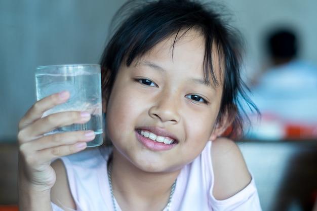 Asiatischer mädchengriff des lächelns kinderein glas eiswasser