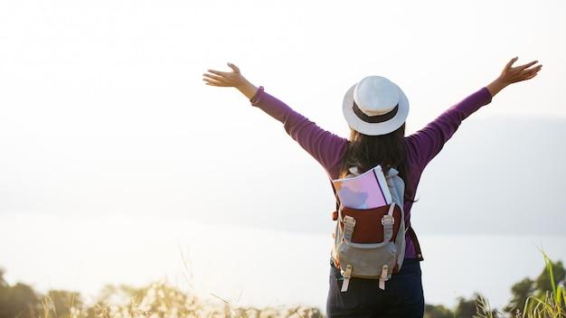 Asiatischer mädchenrucksack, der sonnenuntergang auf berg genießt. entspannen sie sich zeit auf ferienkonzeptreise