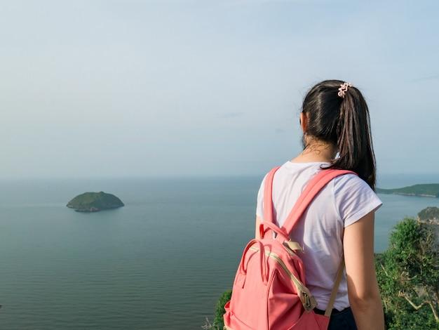 Asiatischer mädchentourist mit rosa tasche, reise allein im natur-platz.