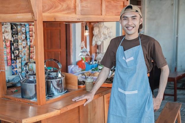 Asiatischer männlicher angkringanverkäufer in der schürze lächelt, die in der seite des wagenstandes steht