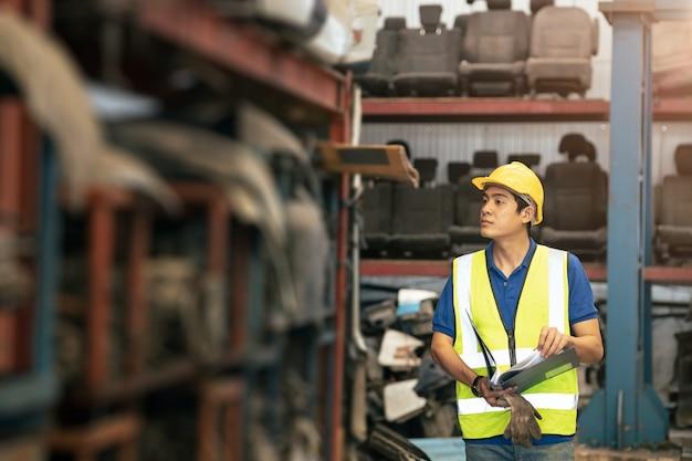 Asiatischer männlicher arbeiter, der daran arbeitet, den lagerbestand der produkte im lagerregal zu überprüfen