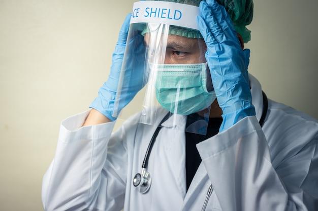 Asiatischer männlicher arzt, der gesichtsschutz und uniform mit stethoskop trägt