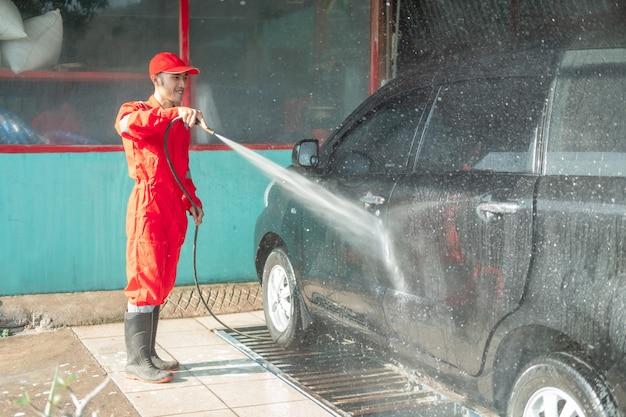 Asiatischer männlicher auto-reiniger, der rote uniform trägt, sprüht wasser, während das auto im autosalon gewaschen wird