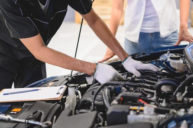 Asiatischer männlicher automechaniker überprüfen automotor-zusammenbruchproblem vor automobil