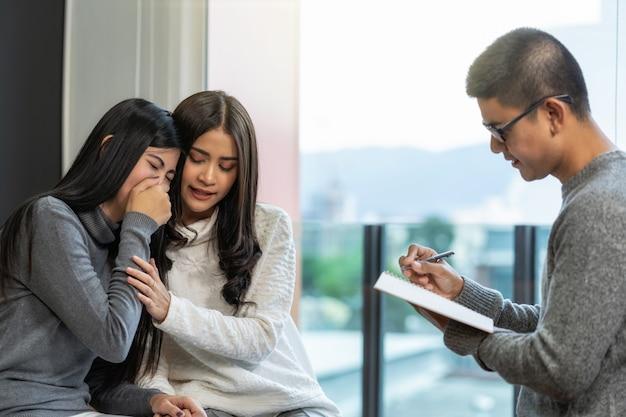 Asiatischer männlicher berufspsychologendoktor, der den lesbischen liebhaberpatienten die beratung gibt