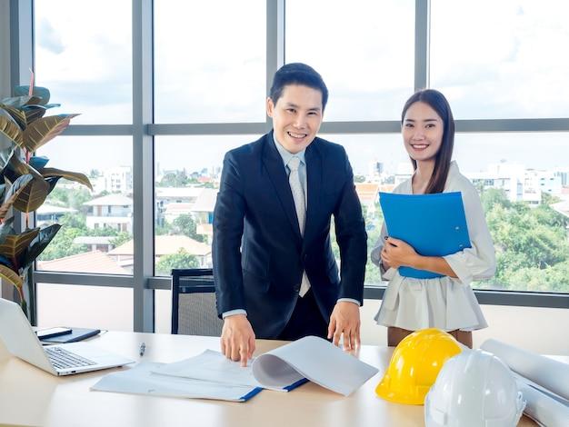 Asiatischer männlicher chefarchitekt oder ingenieur im anzug und junge sekretärin diskutieren auf blaupause mit laptop-computer und weißen und gelben schutzhelmen auf schreibtisch auf riesigem glasfenster im büro.