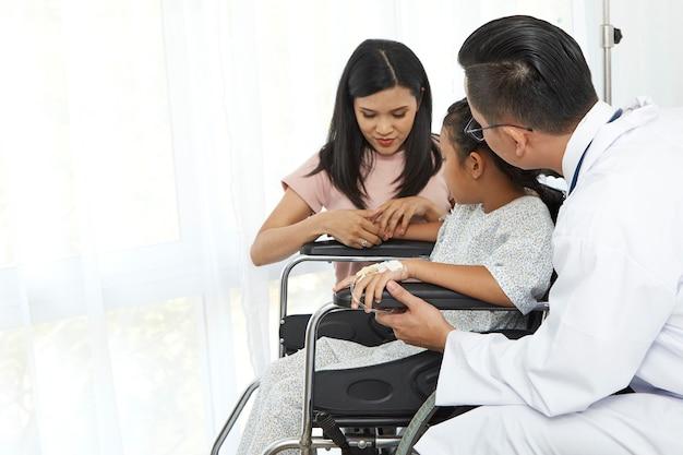 Asiatischer männlicher doktor, der mit kleinkindrollstuhl und -mutter, konzeptkrankenhauspflege spricht